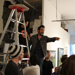 Writer/director Ben Ratner directs a crowd scene at the art gallery